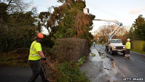 Workers remove fallen trees from powerlines in the village of Grafty Green in Kent on 30 December 2013