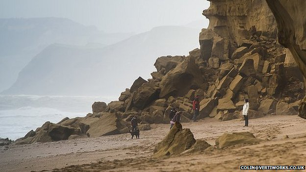 A family playing close to the rock fall on Hive Beach