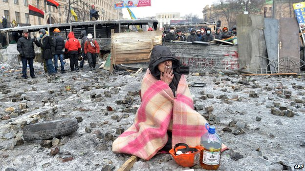 A protester smokes at the barricade in front of armour-clad security forces blocking access to the Verkhovna Rada parliament in Kiev