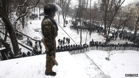 A demonstrator looks down at a cordon formed by Interior Ministry members during a rally by pro-European integration protesters in Kiev
