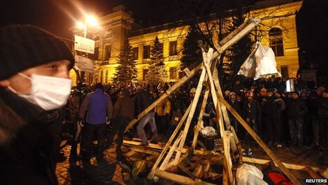 Pro-European integration protesters build a catapult to throw stones during clashes with police in Kiev on 20 January 2014