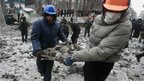 Demonstrators carry stones during a rally held by pro-European integration protesters in Kiev on 21 January 2014