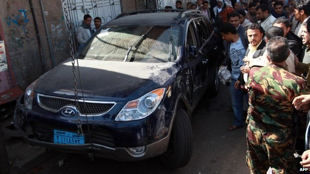 People inspect the car in which Ahmed Sharaf al-Din was shot dead in Sanaa (21 January 2014)