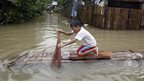 A boy uses a broom to paddle a piece of wood that he is using as a raft along a flooded road in Butuan City.