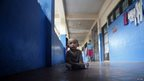 Boy resting in the corridor of a school turned into an evacuation centre.