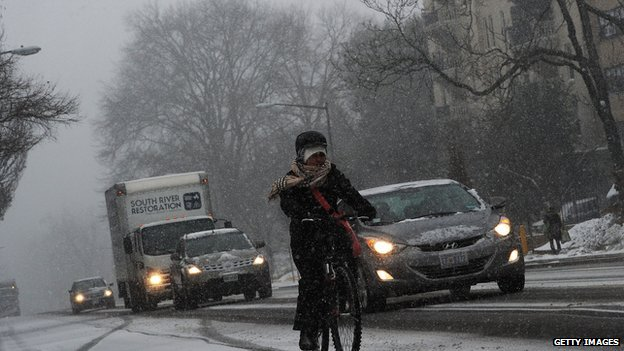 Commuters make their way under a snowfall on January 21, 2014 in Washington, DC