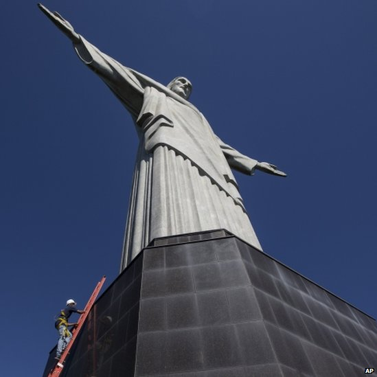 A worker climbs the Christ Redeemer statue to examine recent damage (21 January 2014)