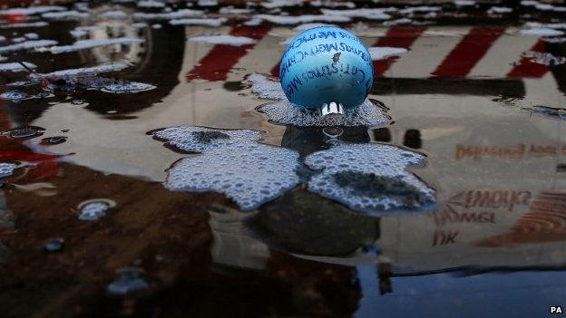 Reflection of van driving past Christmas bauble floating in water
