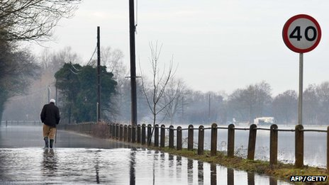 Man walking on flooded road in Yalding