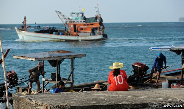 A woman sits at a pier as Thai fishermen venture out