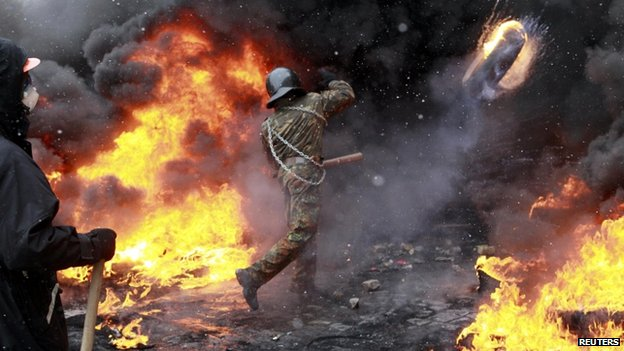 Protester throws burning tyre in Kiev (22 January 2014)