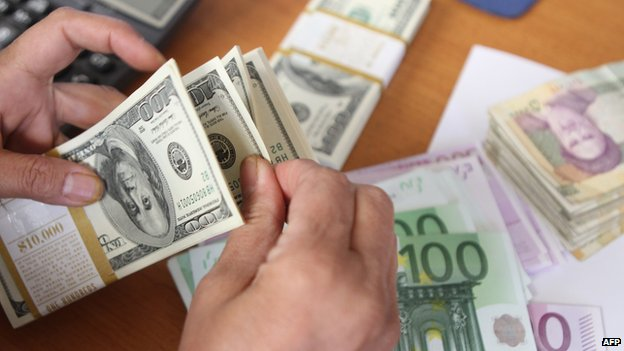 Man counts money, including dollars, euros and Iranian rials