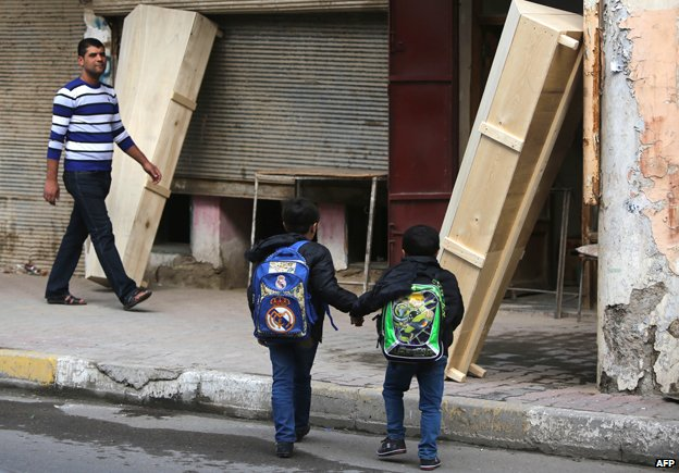 Children outside a coffin-maker's shop in central Baghdad
