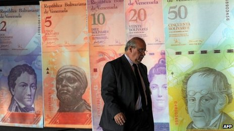 A man walk in front of posters of Venezuelan bills in Caracas