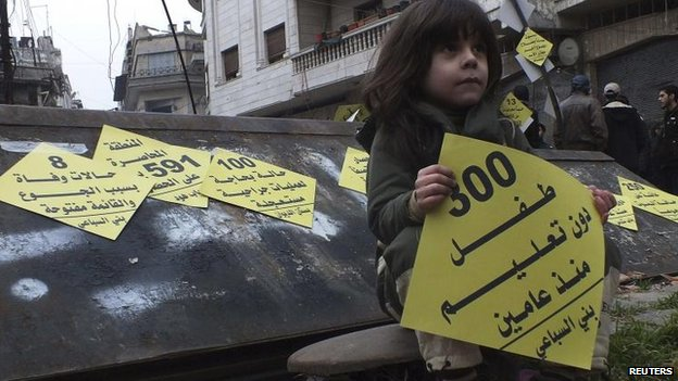 "A girl carries a sign that reads ""300 children without education since two years"" during a campaign organised by activists in the besieged area of Homs, 22 January, 2014"