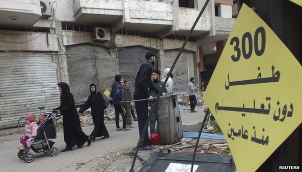 "Civilians walk past a sign that reads ""300 children without education for two years"" in the besieged area of Homs"