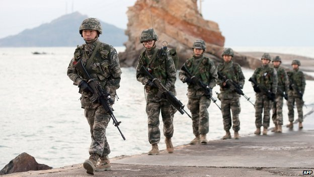 South Korean soldiers patrol on the South-controlled island of Yeonpyeong near the disputed waters of the Yellow Sea at dawn on 21 November 2013