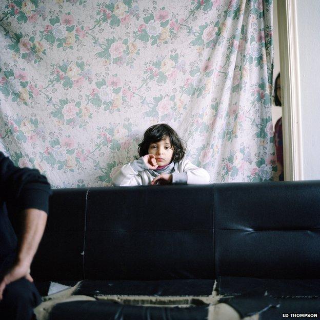 Girl behind sofa