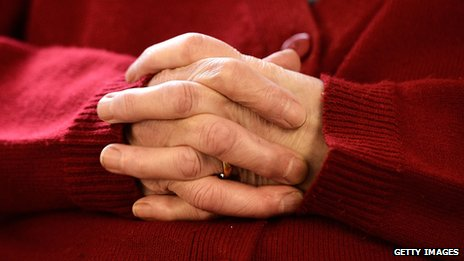 An elderly person interlocks their fingers