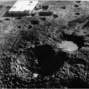 The crater on Ashley Walk created by the Grand Slam in the New Forest on 13 March 1945 - with the target building in the background