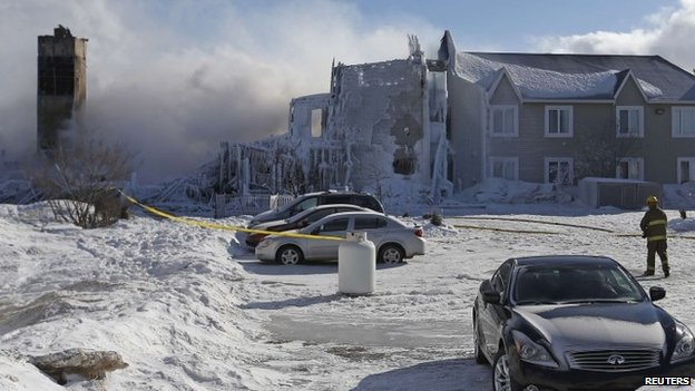 A firefighter walks past the Residence du Havre after a fire in L'Isle-Verte, Quebec, 23 January 2014