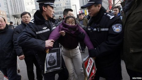 Liu Chunxia, a supporter of Xu Zhiyong, is detained by policemen while she gathers with other supporters nearby a court where Mr Xu's trial is being held in Beijing, 22 January 2014
