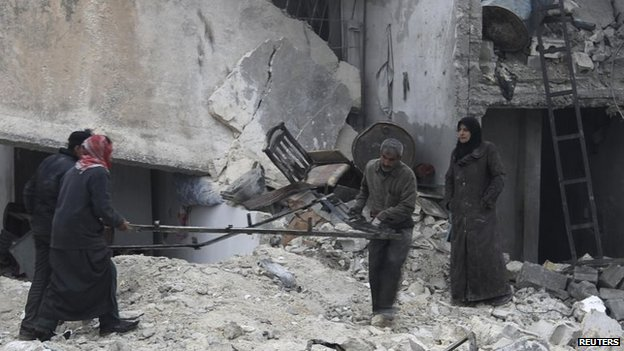 Civilians carry belongings from rubble after what activists said was shelling by government forces in Aleppo
