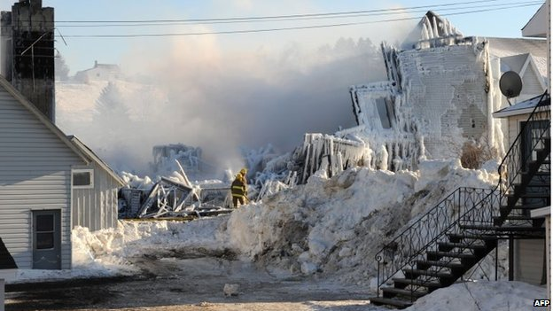 Smoke rises from the burnt and now frozen remains of a retirement home in L'Isle-Verte on 23 January 2014.