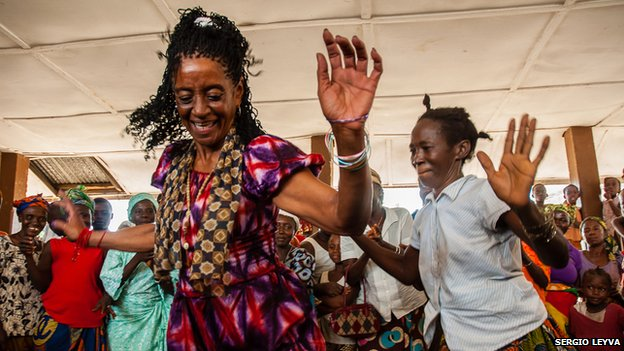 Elvira Fumero dances with villagers in Mokpangumba