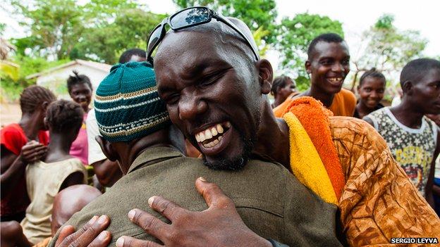Alfredo Duquesne and Sierra Leone villager embrace in Mokpangumba
