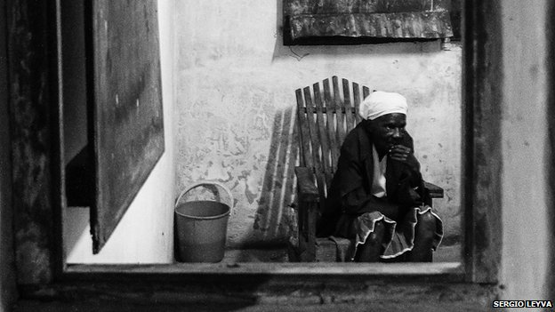 Lone woman photographed through window in Perico