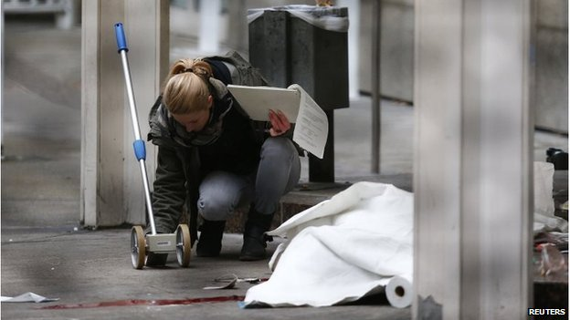 A police officer examines the crime scene next to a covered body, after a double murder at the state court in Frankfurt.