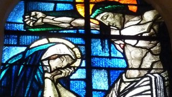 Jesus Christ on cross on stained glass window of a church