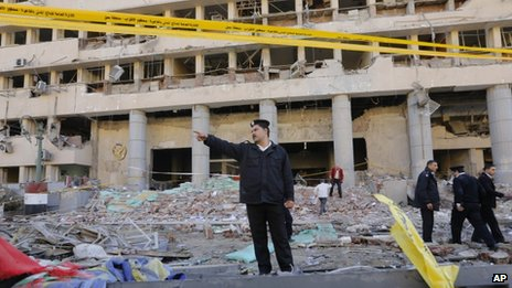 An Egyptian policeman shouts at bystanders to keep away from the site of a blast at the Egyptian police headquarters in downtown Cairo, Egypt, Friday, Jan. 24, 2014.