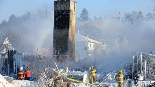 Canadian firefighters douse the burnt remains of a retirement home in L'Isle-Verte on 23 January 2014