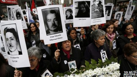 "Demonstrators hold up images of their relatives, who were victims of human rights abuse during the former General Augusto Pinochet years, in front of the ""La Moneda"" Presidential Palace during a rally in Santiago September 11, 2013."