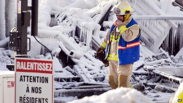 "An emergency worker walked past a sign that reads ""Look out for our residents"" in French amid icy rubble in L'Isle-Verte, Quebec, on 24 January 2014"