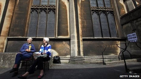 Two women wearing party rosettes sitting outside a church