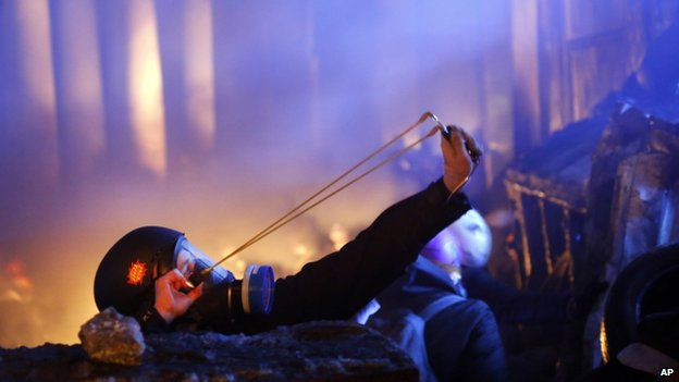 A protester uses a slingshot during clashes with police in central Kiev, early 25 January 2014