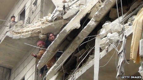 Syrians inspect the damage following a reported government airstrike on the northern Syrian city of Aleppo on 23 January 2014.