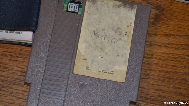 A grey Nintendo cartridge. The label is ripped off and Mario has been written on in pen.