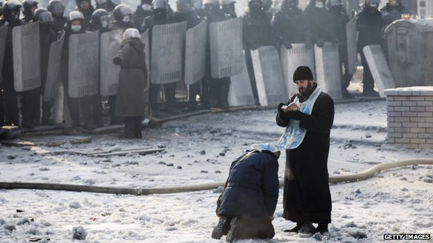 Man kneels before an Orthodox priest in front of riot police (25 January 2014)