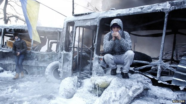 Demonstrator in a burnt-out bus in Kiev (25 January 2014)