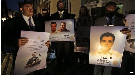 Demonstrators hold placards with pictures of Al-Jazeera journalist Abdullah Al Shami and cameraman Mohammad Badr (12/11/13)