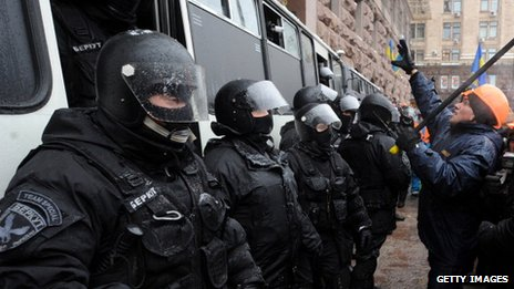One of the anti-Yanukovych protesters addresses Berkut anti-riot police force officers in Kiev, on December 11, 2013.