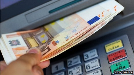 A hand withdrawing euro notes from a cashpoint