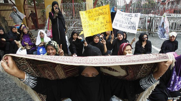 Filipino Muslim women hold placards during a rally urging the government to hold a round of peace talks with the MILF outside the Presidential Palace in Manila (June 28, 2013)