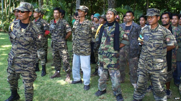 Thirty Muslim rebels from the Moro Islamic Liberation Front (MILF) led by Alvin Conto (Left) surrender to Philippine Army officers and Iligan City officials at the 104th Infantry Brigade Philippine Army base in Iligan city on August 21, 2008