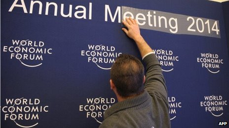 A man prepares a sign for the WEF annual meeting