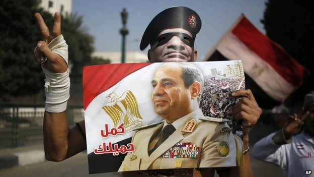 "An Egyptian man holds a poster and a mask depicting Egyptian army chief Gen Abdel Fattah al-Sisi with Arabic that reads, ""complete your good deed,"" near Tahrir Square in Cairo on Saturday"